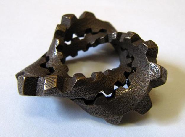 "Trefoil with Cogs 3d printed Stainless steel with ""antique bronze glossy"" finish, from the side."