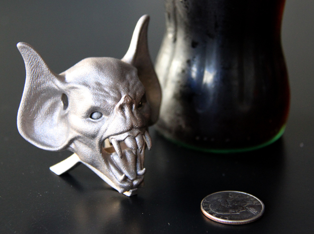 Vampire Head Bottle Opener 3d printed The vamp head bottle opener shown here on it's stand, next to a bottle and coin for size comparison.