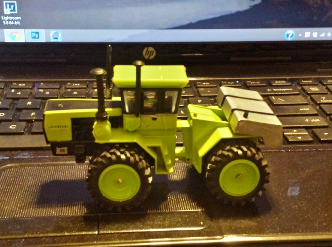 mounted on a Steiger tractor painted silver and with straps