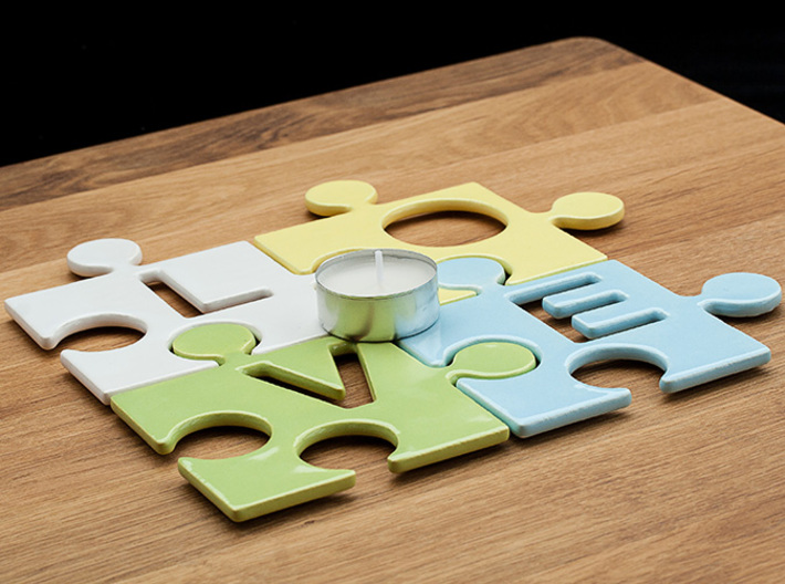 """Puzzle Piece V - """"Love-letters"""" 3d printed 4 puzzle pieces combined to write the word """"love"""". With a tealight for size reference."""