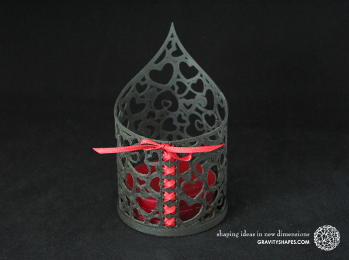 Pointed tealight holder with hearts 3d printed The photo shows its own print (FDM print) made of black wood with decorative lacing.