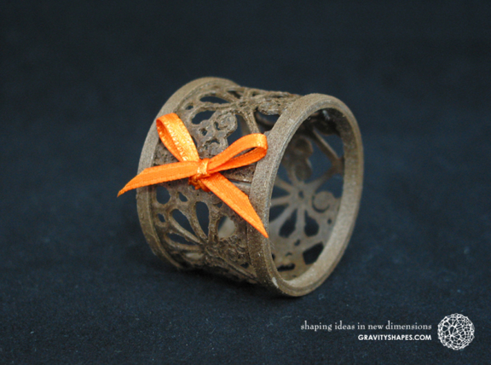 A small napkin ring with Mosaic-3b 3d printed The photo shows an own print (FDM print) made of brown wood incl. decorative lacing.