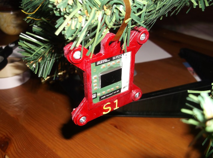 Socket S1 CPU Bauble Single 3d printed A decorated test print of the CPU Bauble, as viewed from the front. The PCB has black boxes containing the model number of the CPU.