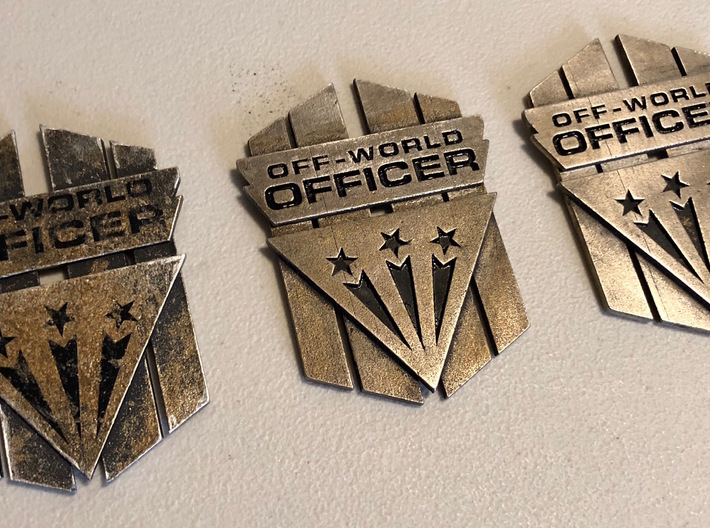 Off-World Officer Badge 3d printed The original badge from the movie shown left and a pair of the available prints on the right.
