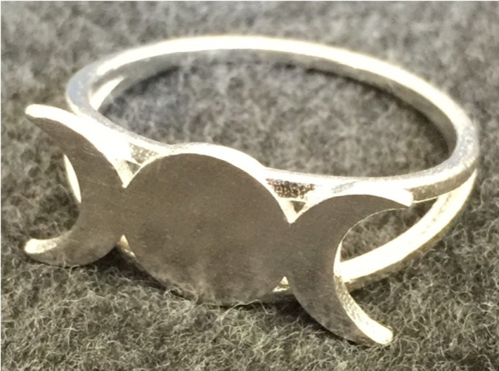 """Triple Moon Ring 3d printed The Triple Moon ring in raw silver; """"raw"""" means unpolished. You can see the reflection of the felt backdrop in its surface."""