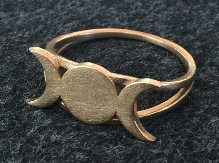 Triple Moon Ring 3d printed The ring in raw brass. All the unpolished materials have a rough textured surface.
