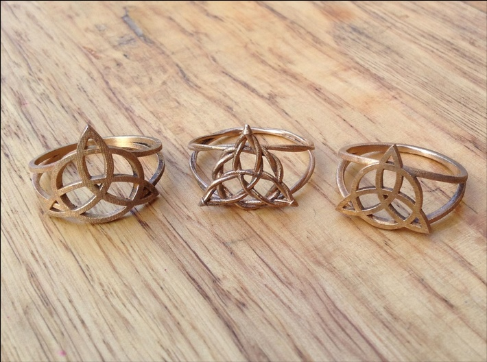 Woven triquetra (choose size) 3d printed The three Kickin' Wiccan styles of triquetra ring, side-by-side so you can compare. All three are in raw bronze. The woven style costs more, because it takes me longer to adjust the band for individual ring sizes.