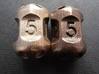Five sided 'pepperpot' dice 3d printed Current version in stainless steel on left, previous version in polished bronze steel on right.
