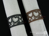 A large napkin ring with Hearts  3d printed The photo shows an own print (FDM print) made of brown and black wood incl. decorative lacing.