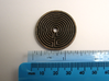 Labyrinth coin 3d printed shown with metric and imperial scales. Coin is 35 mm,  approx 1 and 6/16th inches across